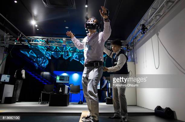 A member of the media wearing an HTC Corp Vive virtual reality headset tries the Extreme Courage Test Machine Fear of Heights The Show VR attraction...