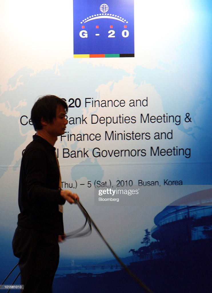 A member of the media works in front of a sign for the G20 Finance Ministers and Central Bank Governors Meeting at the media center for the meeting in Busan, South Korea, on Thursday, June 3, 2010. The meeting will be held through June 5. Photographer: Tomohiro Ohsumi/Bloomberg via Getty Images