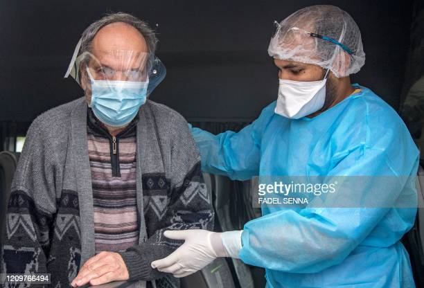 A member of the medical staff helps a patient as he leaves a hospital after recovering from the Covid19 disease caused by the novel coronavirus in...