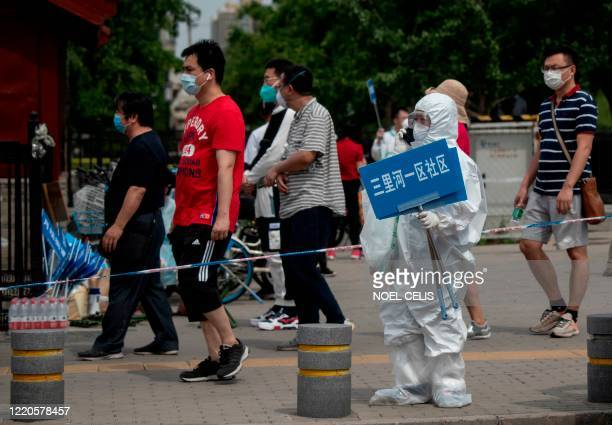 A member of the medical staff in full protective gear holds up a sign to assist people who live near or who have visited the Xinfadi Market a...