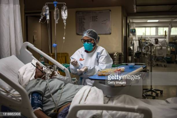 Member of the medical staff serves fruit to a Covid-positive patient in the ICU ward at the Holy Family hospital on May 06, 2021 in New Delhi, India....