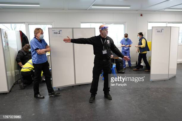 Member of the medical support staff directs members of the public at the Askham Bar Mass Vaccination Centre in York on January 18, 2021 in York,...