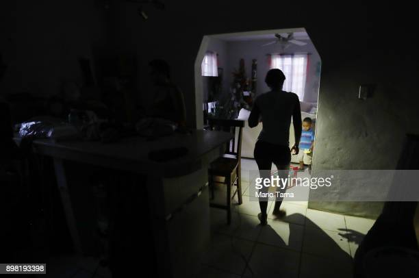A member of the Medina family holds her cell phone for light before dinner on Christmas Eve on December 24 2017 in San Isidro Puerto Rico Most of the...