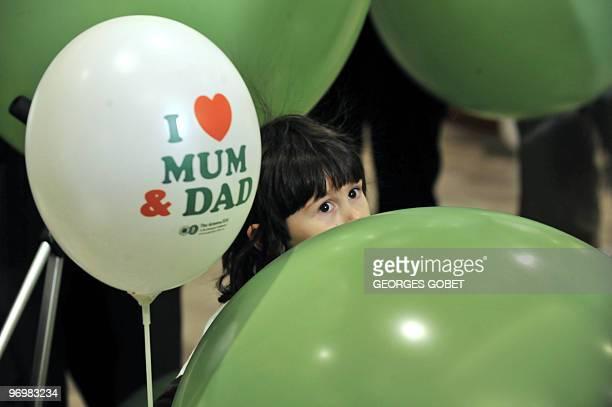 A member of the MEP greens party's child looks up between ballons during a demonstration by parents supporting the party's bid for fathers to obtain...