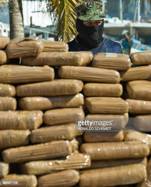 A member of the Mexican Navy stands guard as 823925 Kgs of seized cocaine are prepared to be incinerated on June 25 at the naval base in Yucalpeten...