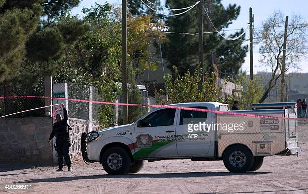 A member of the Mexican police stands guard at the entrance of a house in which eight members of a family were killed by gunmen in Ciudad Juarez...