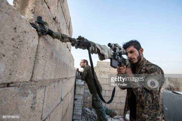 Member of the MFS scans the area for ISIS positions from the roof of their nocter on August 17. 2017 on the western front lines of Raqqa, Syria. The...