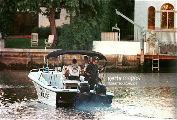 Member of the Miami Beach police SWAT team patrols a canal in the vicinity of a houseboat in Miami Beach, Florida 23 July after it was reported that...