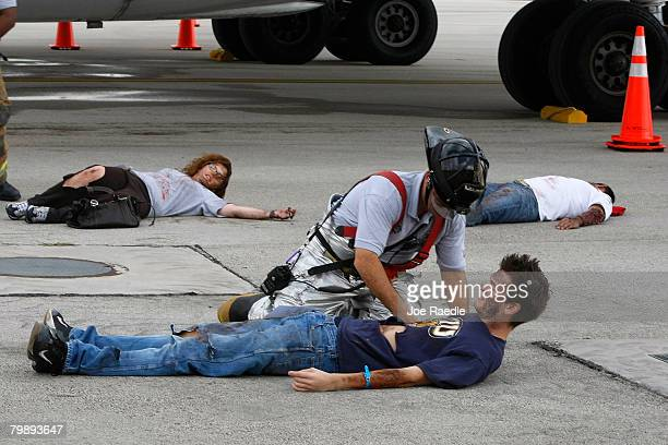 A member of the MiamiDade Fire Rescue team works on a person posing as a victim of an airplane crash during the Miami International Airport's...