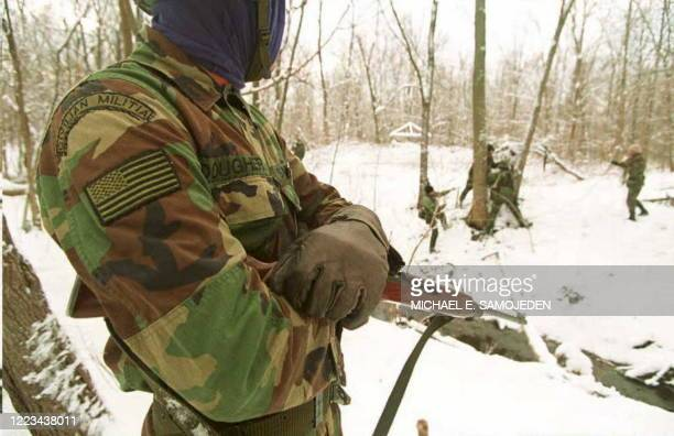 Member of the Michigan Militia watches as fellow survivalists train 11 December 1994 in northern Michigan. The leader of the Michigan Militia, Norman...