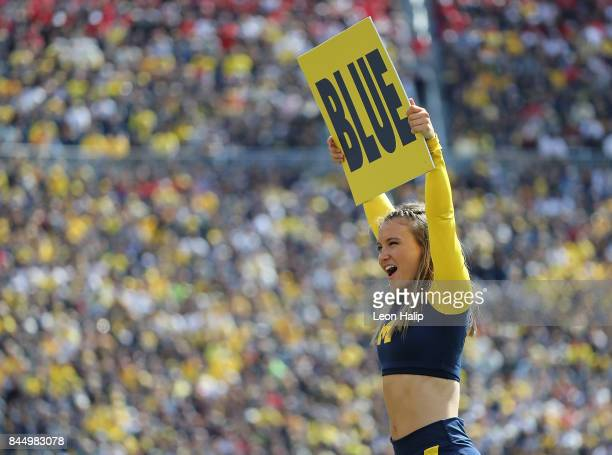 A member of the Michigan Wolverines cheer team performs during the fourth quarter of the game against the Cincinnati Bearcats at Michigan Stadium on...
