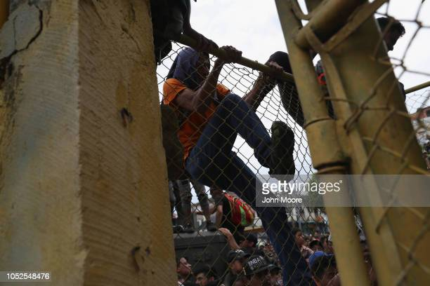 A member of the migrant caravan climbs over a fence on the Guatemalan side of a bridge to Mexico on October 19 2018 in Ciudad Tecun Uman Guatemala...