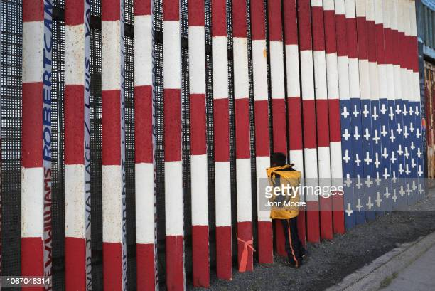 A member of the migrant caravan looks throug the USMexico border fence on November 30 2018 in Tijuana Mexico Authorities closed an openair shelter...