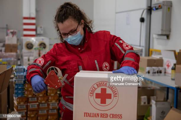 Member of the Milan Committee of the Italian Red Cross seals a box of food and supplies which will be distributed to a network of food banks across...