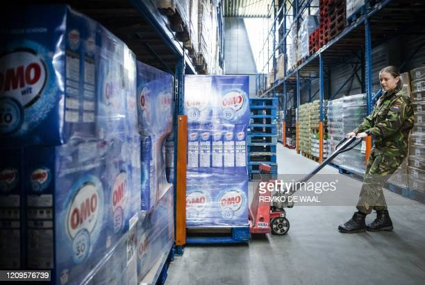 Member of the military manouvers a pallet of washing powder as she helps to restart a foodbank in The Hague on April 10 after a number of foodbanks...