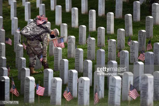 A member of the military places a flag near a headstone at Arlington National Cemetery in advance for Memorial Day on Thursday May 21 2020 in...