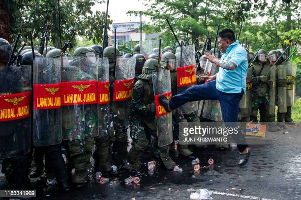 TOPSHOT A member of the military playing the role of protester challenges a line of Indonesian Navy frogmen and commandos during an antiterror drill...
