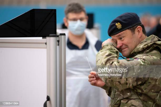 Member of the military reacts after taking a coronavirus test at Merthyr Tydfil Leisure Centre on November 21, 2020 in Merthyr Tydfil, Wales. From...
