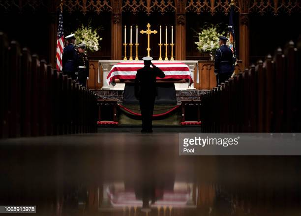 A member of the military salutes the flagdraped casket of former President George HW Bush as it lies in repose at St Martin's Episcopal Church on...