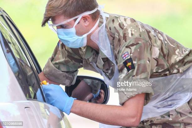 A member of the military takes a swab at a drivein COVID19 testing centre at Chessington World of Adventures Resort theme park on April 24 2020 in...
