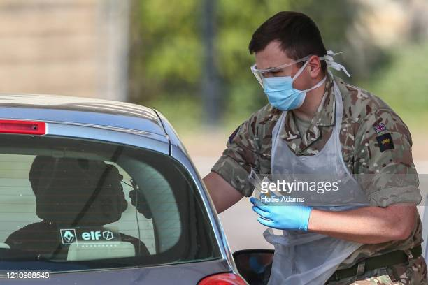 Member of the military takes a swab from a person at a drive-in COVID-19 testing centre at Chessington World of Adventures Resort on April 25, 2020...