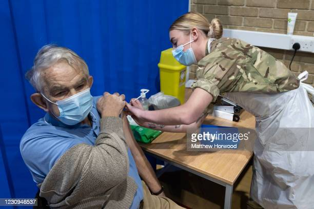 Member of the military vaccinates a man at the COVID-19 mass vaccination centre at Pentwyn Leisure Centre on February 3, 2021 in Cardiff, Wales....