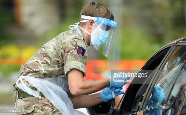 Member of the military wearing a protective face mask and screen, disposable gloves and a plastic apron, takes a swap at a coronavirus drive-through...