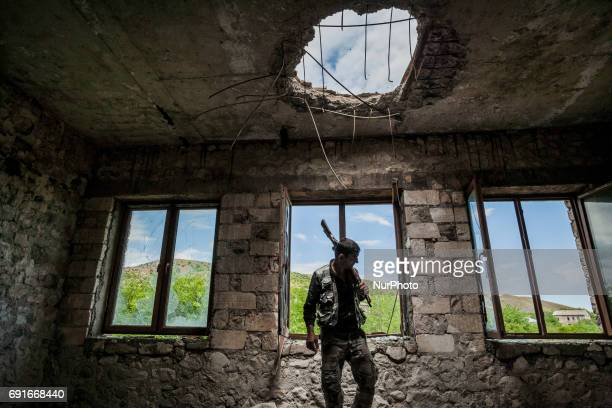 Member of the militia of Nagorno Karabakh in the destroyed school of Talish village on 2 June 2017 shelled with artillery by the Azerbaijan army one...