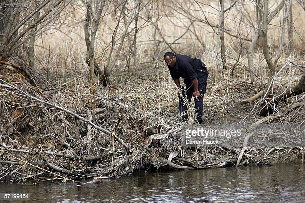 A member of the Milwaukee Police department searches along the banks of the Milwaukee river for missing boys Quadrevion Henning and Purvis Virgina...