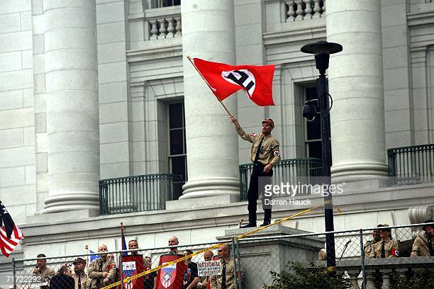 A member of the Minneapolis based National Socialist Movement waves a Nazi flag during a rally at Madison's Capital Square August 26 2006 in Madison...