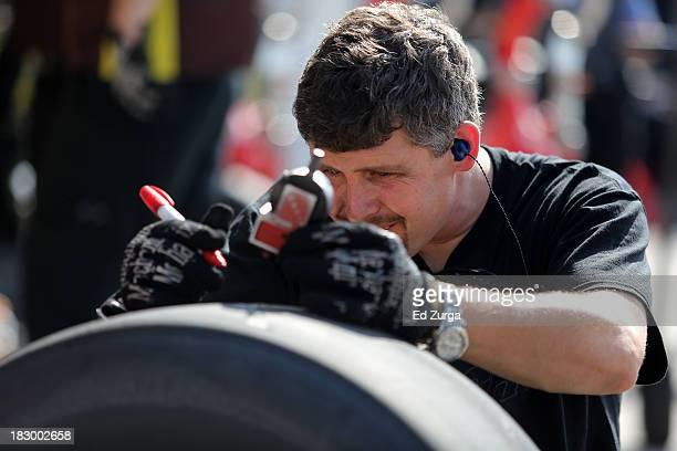 A member of the MM's Toyota works on a tire during testing for the NASCAR Sprint Cup Series at Kansas Speedway on October 3 2013 in Kansas City Kansas