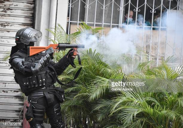 Member of the mobile anti-riot squad shoots at protesters with a tear gas cannister while nurses watch from a window in the La Portada sector on May...