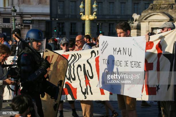 A member of the Mobile Gendarmerie a subdivision of the French national Gendarmerie holds off protesters as they end a demonstration called by the...