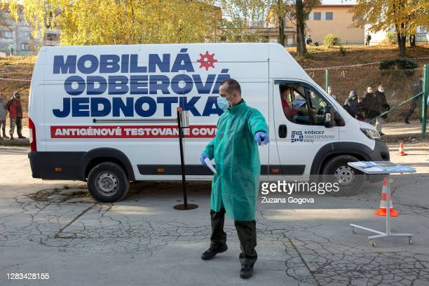 Member of the mobile sampling unit directs people waiting for Covid-19 antigen testing in Lunik IX borough on November 1 in Kosice, Slovakia. Lunik...