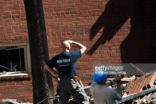 A member of the Montgomery County bomb squad looks at rubble after an explosion at Flower Branch Apartments on August 11 2016 in Silver Spring...