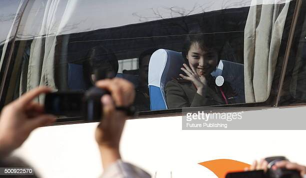 A member of the Moranbong Band a famous North Korean girl band waves to the reporters when leaving the hotel for a rehearsal on December 11 2015 in...