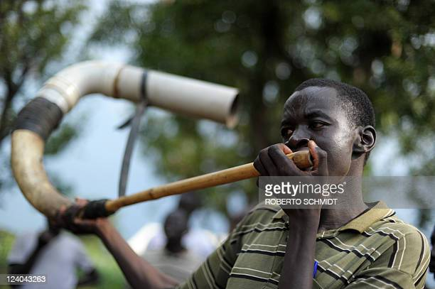 Member of the Mundari ethnic group blows into a horn during a wrestling match in a dusty patch where the tribe brought cattle and sheep for sale in...