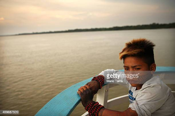 A member of the Munduruku indigenous tribe rides on a boat on the Tapajos River following a 'Caravan of Resistance'' protest by indigenous groups and...