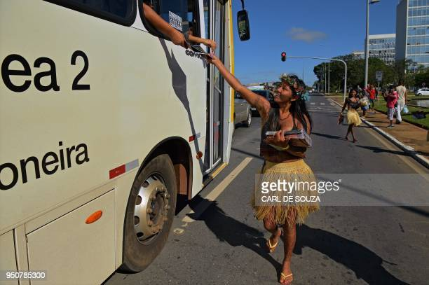 A member of the Munduruku tribe taking part in the Indigenous National Mobilization week gives out fliers to passengers of a bus during a...