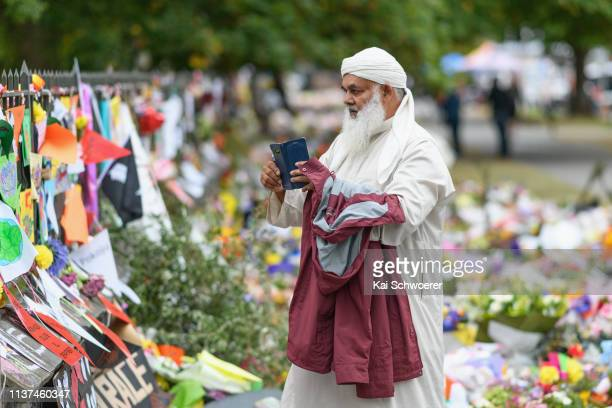 A member of the Muslim community takes a photo as flowers and condolences are seen at the entrance to the Christchurch Botanic Gardens close to Al...