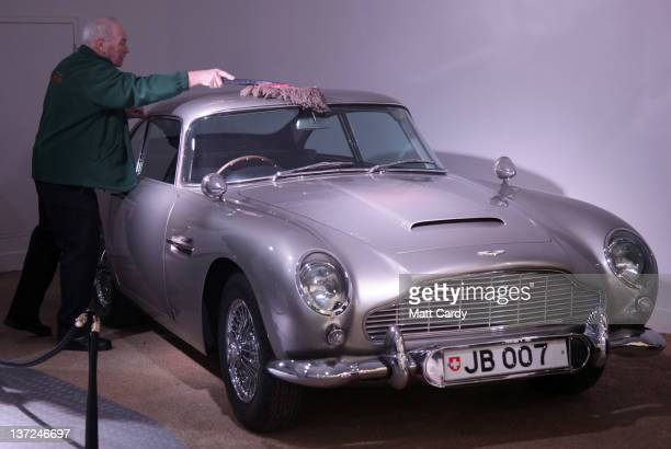 A member of the musuem team attends to a Aston Martin DB5 used in the James Bond film Goldfinger and being displayed at the Bond In Motion exhibition...