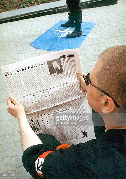 Member of the National Bolshevist Party reads the movement journal as another member stomps on the NATO flag, Rostov-on-Don, Russia, April 5, 2000....
