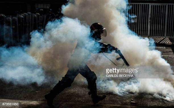 TOPSHOT A member of the National Guard cracks down on opposition demonstrators during a march against President Nicolas Maduro in Caracas on April 26...