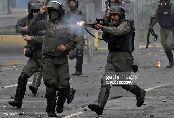 TOPSHOT A member of the national guard fires his shotgun at opposition demonstrators during clashes in Caracas on July 28 2017 Protesters took over...