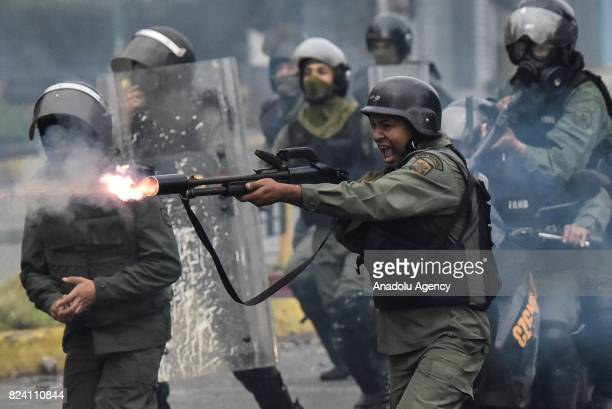 A member of the national guard fires his shotgun at protesters during clashes in Caracas Venezuela on July 28 2017 Protesters took over streets in...