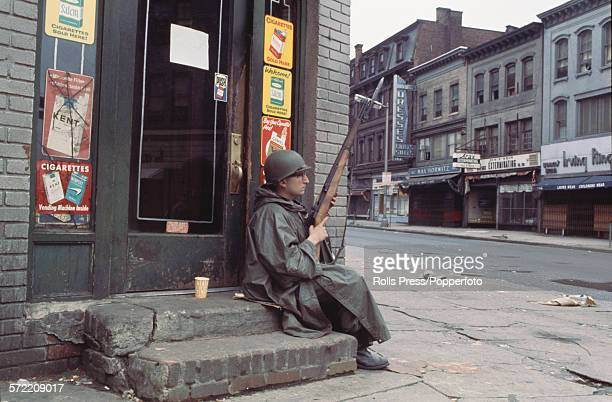 A member of the National Guard of the United States sits with his rifle on the steps of a closed convenience store on a deserted shopping street...