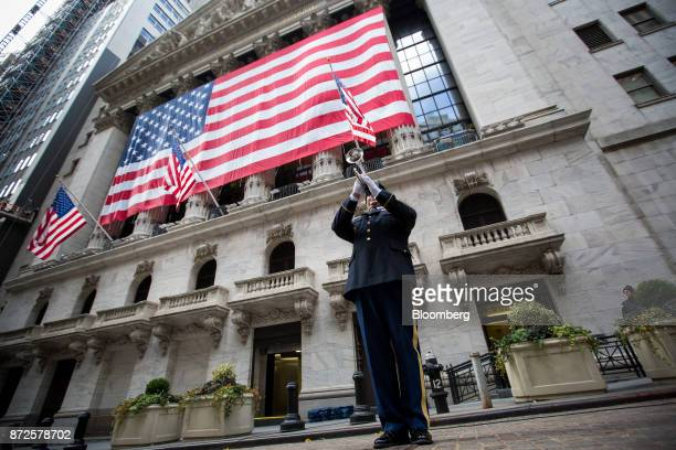 A member of the National Guard plays a trumpet during a flag raising ceremony in honor of Veteran's Day in front of the New York Stock Exchange in...