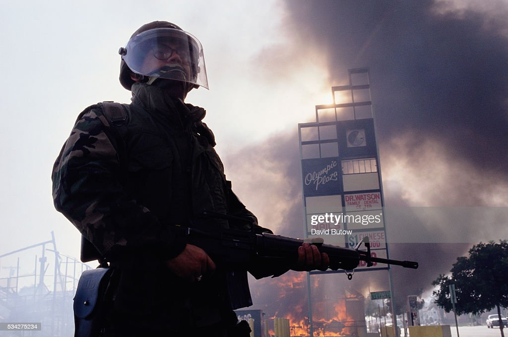 A member of the National Guard stands near burning building during the Los Angeles riots. In April of 1992, after a jury acquitted the police officers involved in the beating of Rodney King, riots broke out throughout South Central Los Angeles, killing 55 people, injuring another 2,000, and causing more than $1 billion in damage.