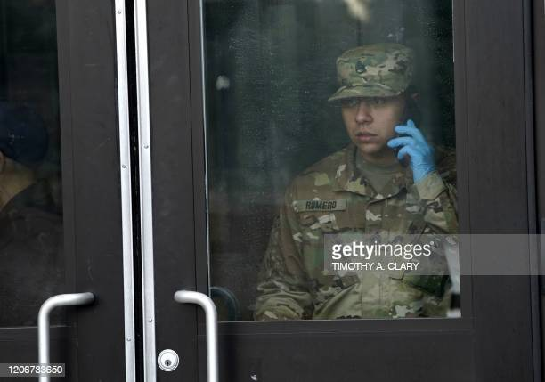 A member of the National Guard talks on a cellphone before giving food to residents of New Rochelle New York at New Rochelle High School March 12...