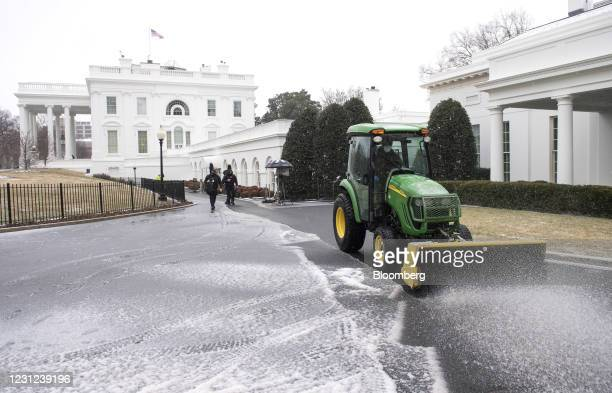 Member of the National Park Service clears snow and ice from the White House in Washington, D.C., U.S., on Thursday, Feb. 18, 2021. After a...